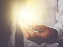 Man Holding Lit Lightbulb