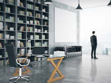 Man in Suit Standing Beside a Bookshelf